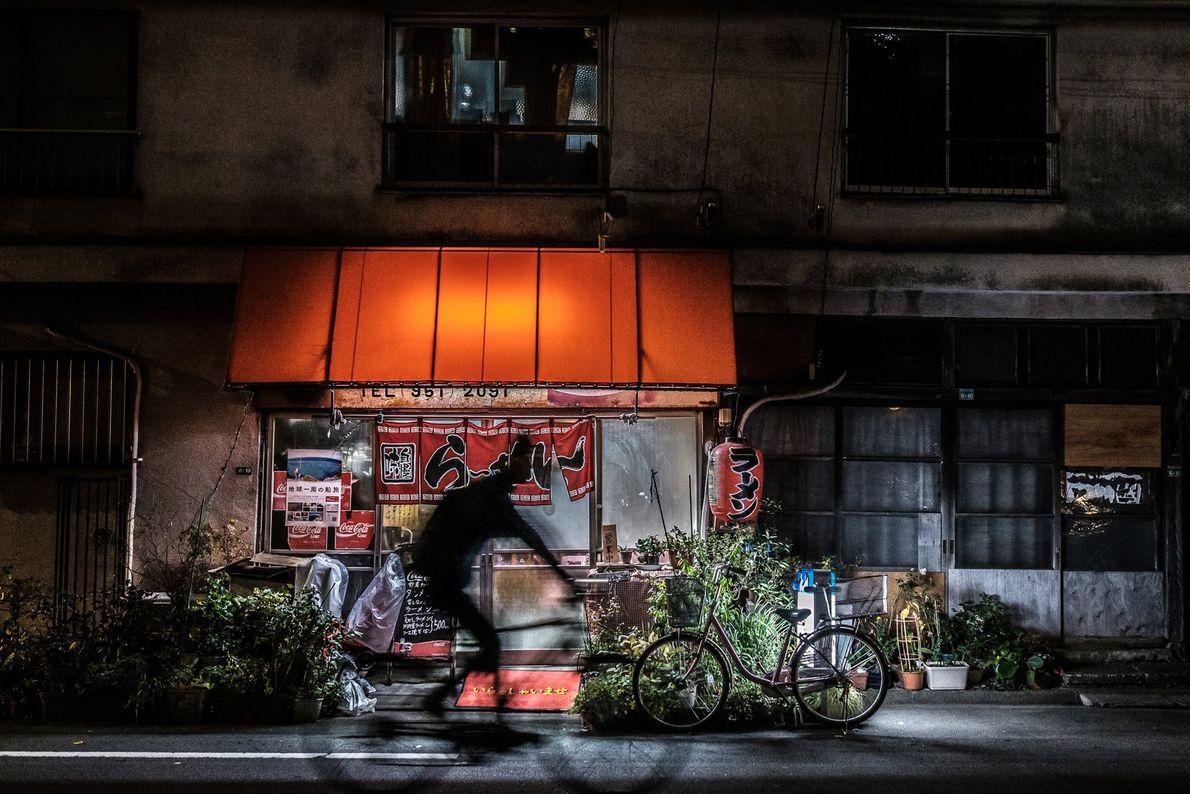 Um ciclista a passar em frente a uma aconchegante loja de ramen, por volta da meia-noite, ...