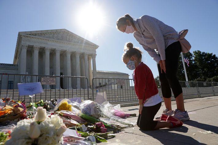 Abby Martin, de cinco anos, e a sua mãe, Jackie, visitam um memorial improvisado para a ...