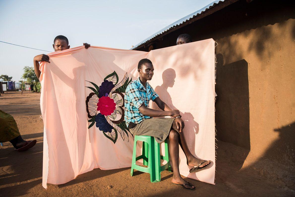 Irene Sonia posa em frente de uma milaya, ou lençol — uma das poucas coisas que ...