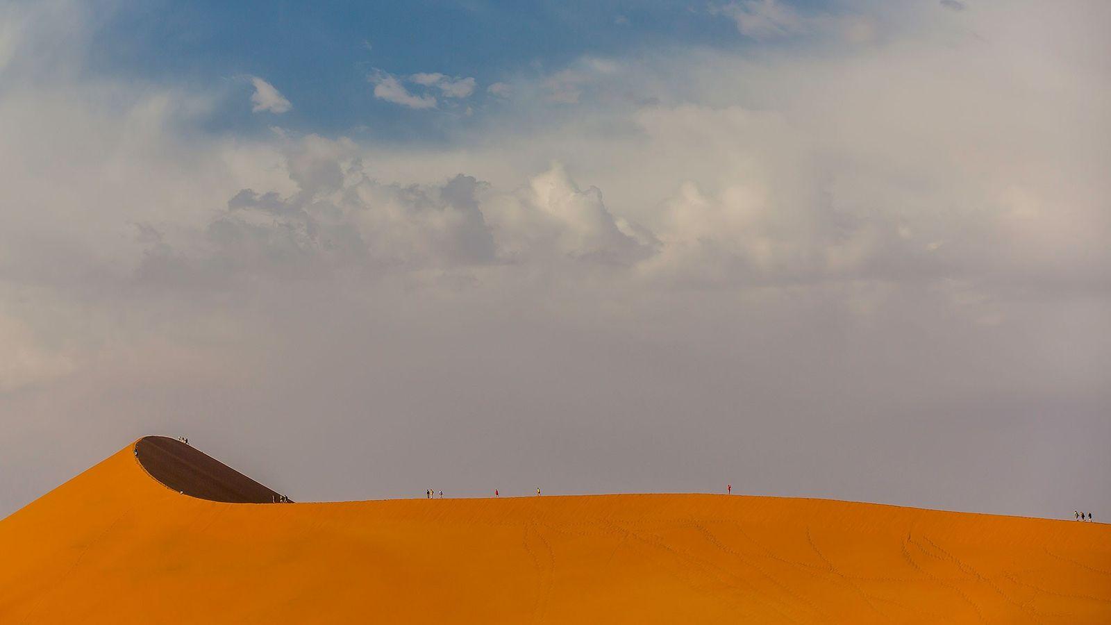 Silhueta dos visitantes na imensidão das dunas do deserto da Namíbia