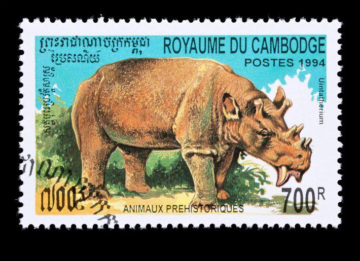 O mamífero extinto Uintatherium, aqui representado num selo postal do Camboja, viveu há cerca de 56 ...