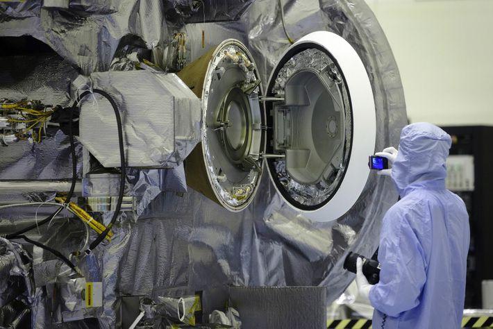 Com a escotilha aberta, um técnico do Centro Espacial Kennedy inspecionava o interior da cápsula de ...