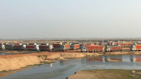 Diariamente, cerca de 300 camiões levam as suas cargas de areia de uma mina no rio ...