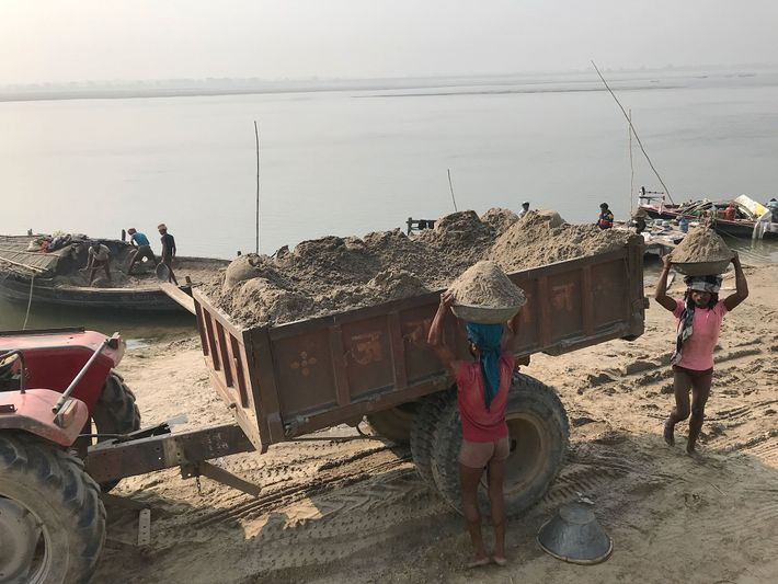 Os mineiros de areia recolhem a sua valiosa mercadoria do rio Ganges, em Utar Pradexe. A ...