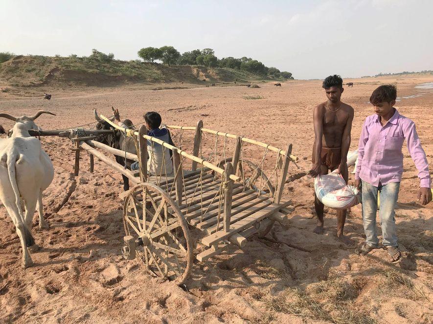 Dois mineiros artesanais de areia carregam a sua carroça, no rio Ken, no norte da Índia.