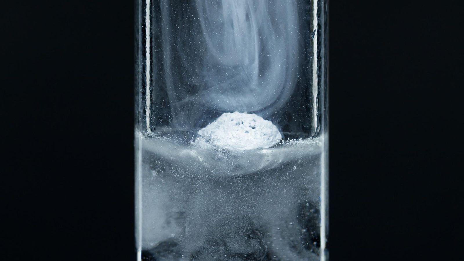 pequena partícula de potássio metálico num tubo de ensaio com água