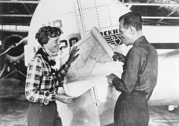 Earhart e o navegador Fred Noonan consultam um mapa do Pacífico que mostra a rota de ...