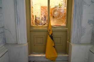 """Uma bandeira """"Não Me Pisem"""" entre as janelas partidas do edifício do Capitólio."""
