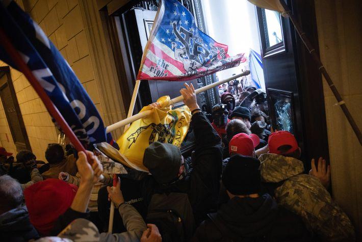 Uma multidão de manifestantes força a entrada no Capitólio, exibindo bandeiras eleitorais de Trump e chapéus ...
