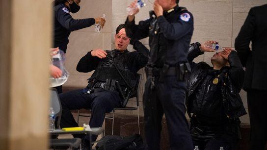 Polícias do Capitólio limpam os olhos após terem sido expostos a gás pimenta.