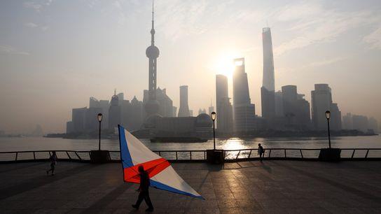 Um homem transporta um kite ao pôr-do-sol, em frente ao inconfundível horizonte de Pudong, na China.