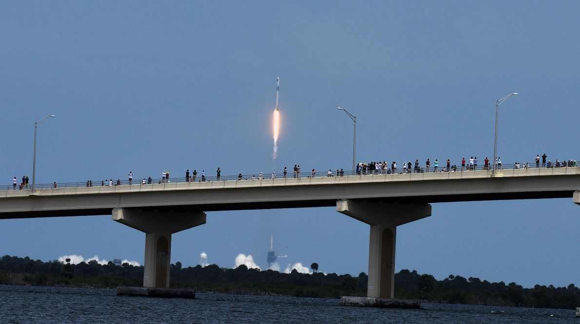 Os espetadores pareciam respeitar o distanciamento social enquanto assistiam ao lançamento do foguetão Falcon 9 da ...