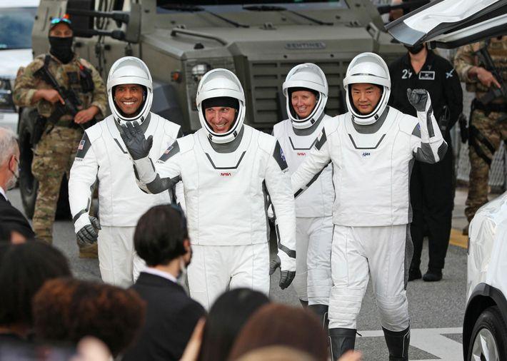 Os membros da tripulação da missão Crew-1, o comandante Mike Hopkins (frente, centro), Victor Glover (esquerda), ...