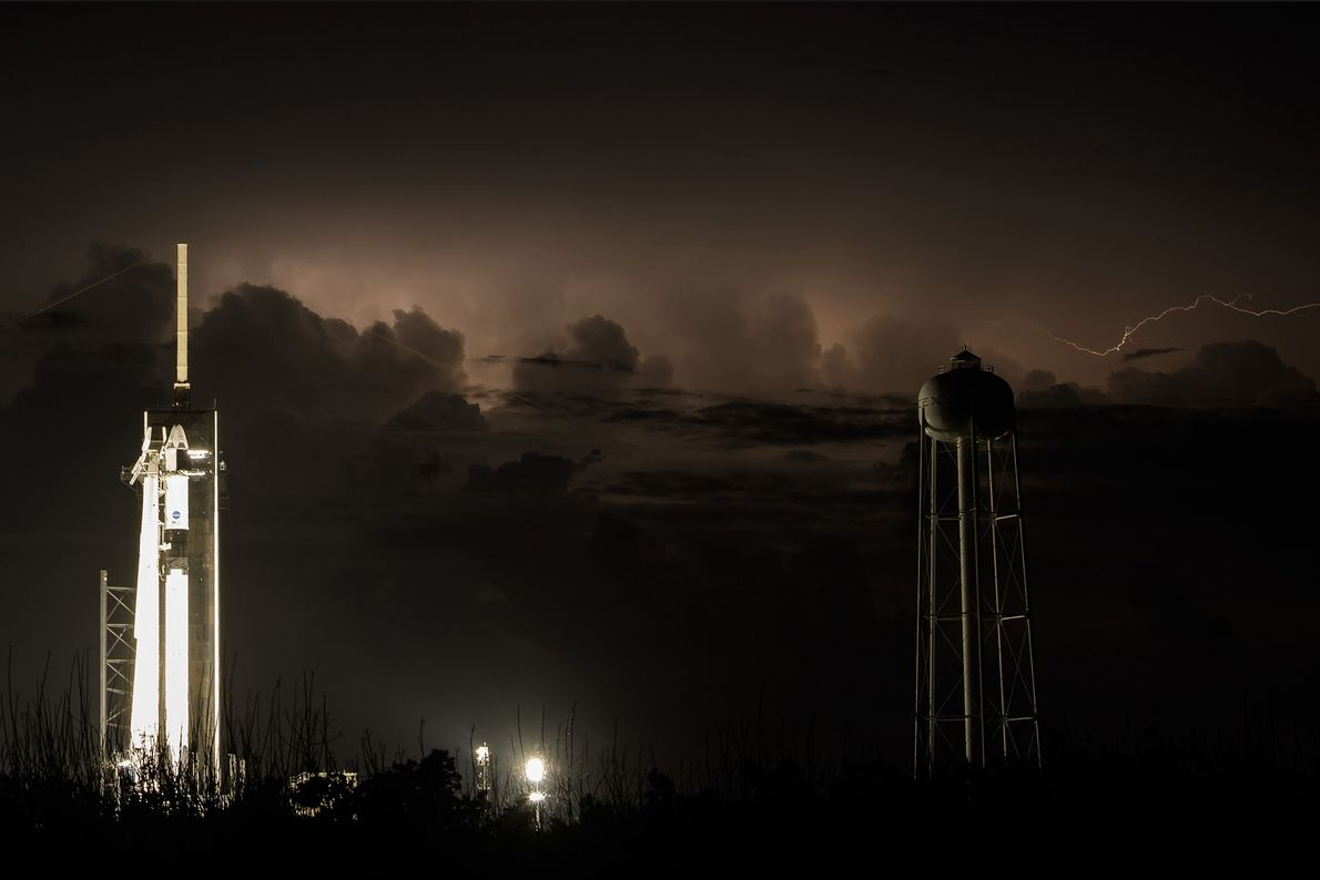 Relâmpagos iluminam o céu da Flórida por trás do foguetão Falcon 9, com a cápsula Crew ...
