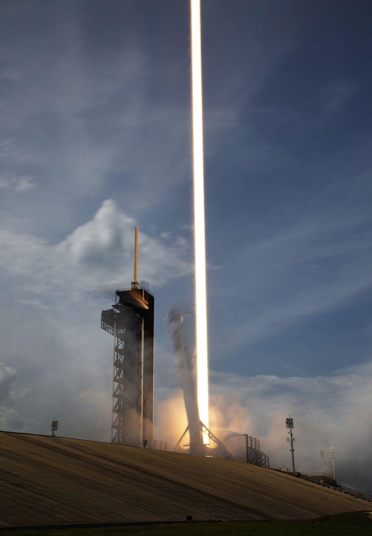 Uma exposição de 15 segundos capta a queima dos nove motores do foguetão Falcon 9 da ...