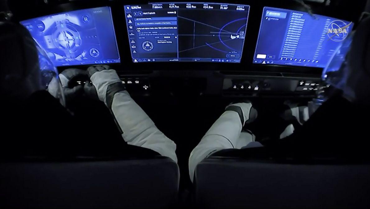 Esta imagem mostra o interior da cápsula Crew Dragon da SpaceX, com os astronautas da NASA ...
