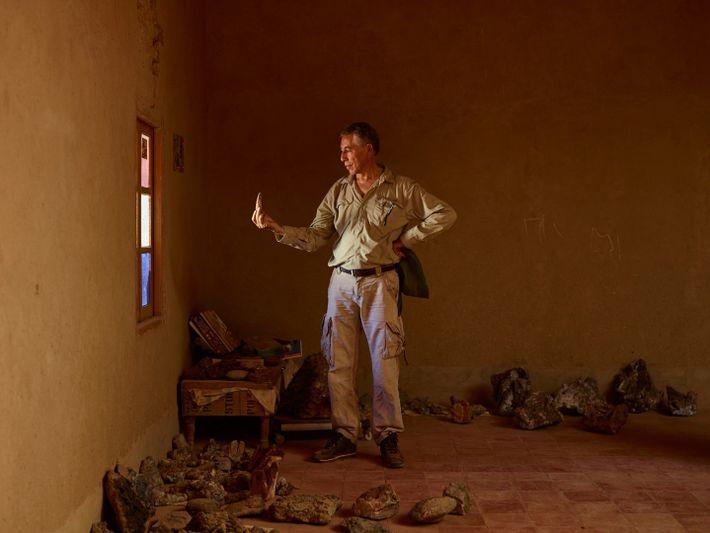 Samir Zouhri examina um dente enorme de espinossauro, na casa de um habitante de Taouz, em ...