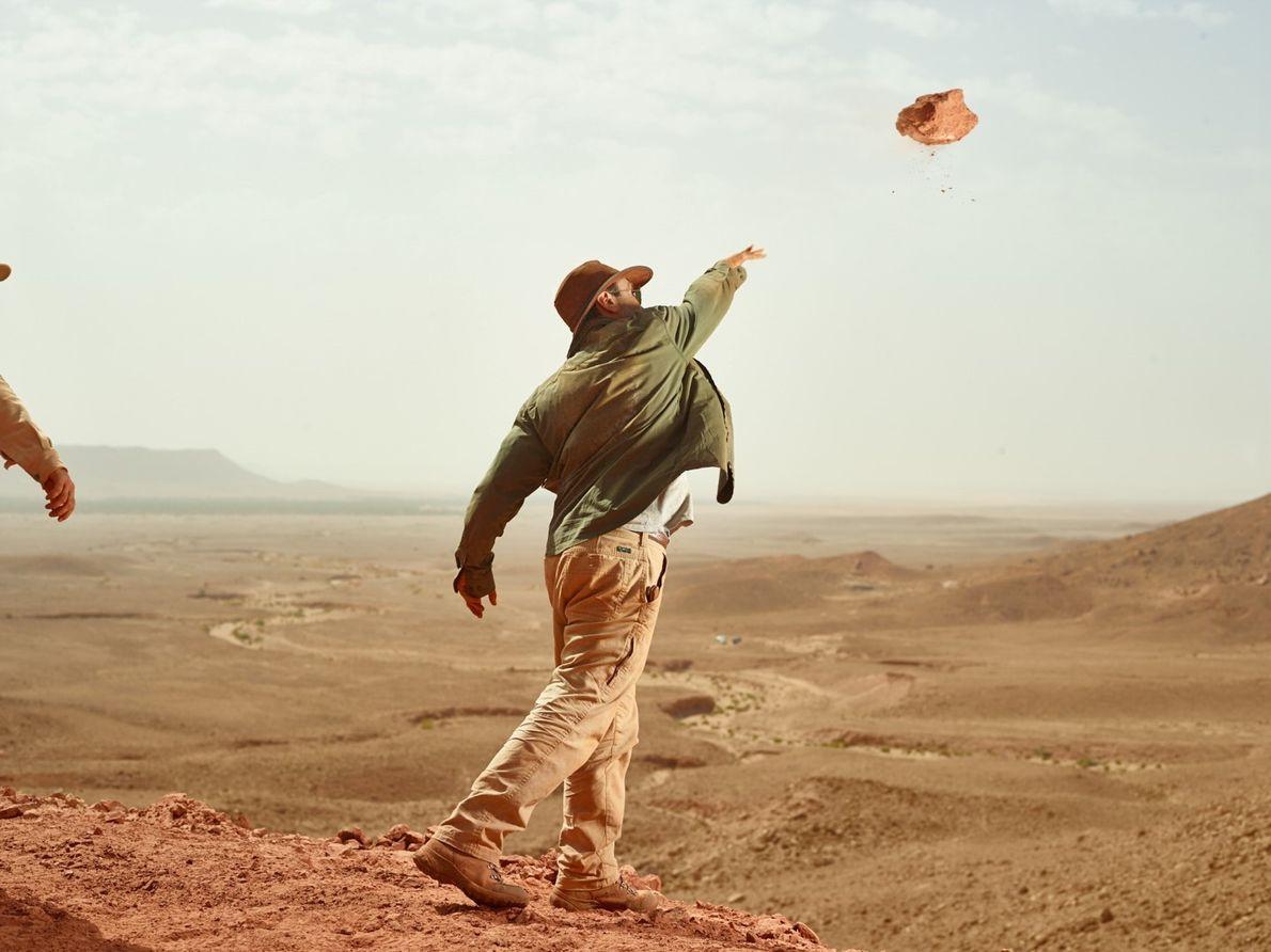 Para limpar o local de escavação do espinossauro de detritos, Ibrahim atira um pedaço de arenito ...
