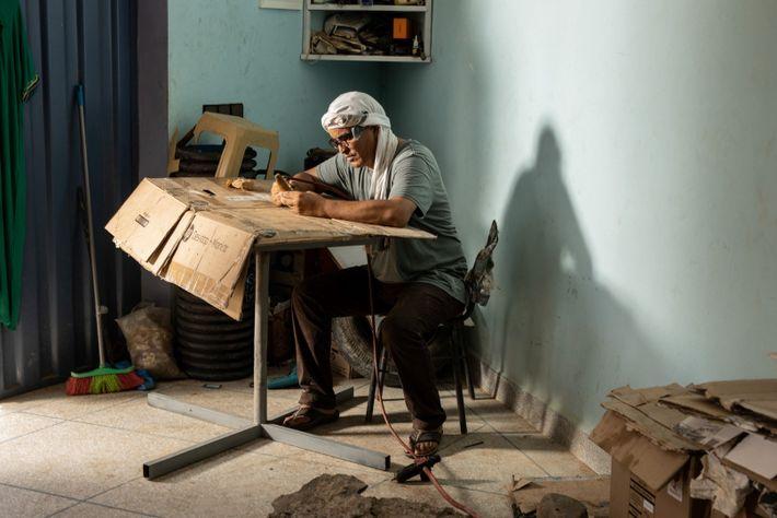 Mohand Ihmadi, proprietário do Centro Ihmadi Trilobites de Alnif, em Marrocos, prepara um dente de espinossauro ...