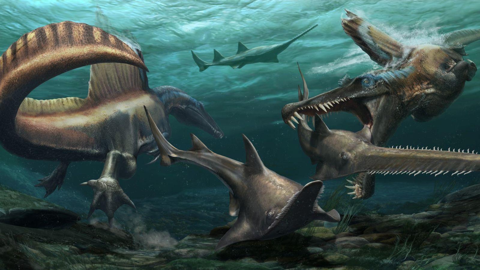 Dois 'Spinosaurus aegyptiacus' caçam o pré-histórico peixe-serra 'Onchopristis' nas águas de um sistema fluvial que, há ...