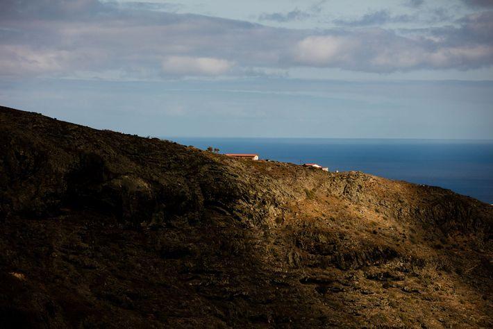 O sol da tarde ilumina uma casa no cimo de um monte de Santa Helena.