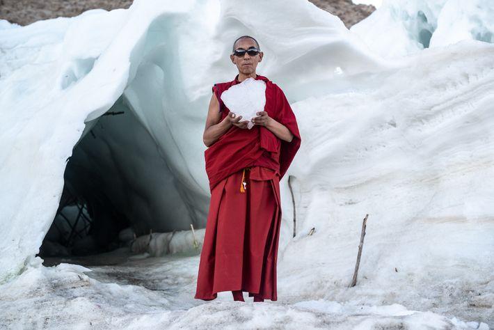 Gyen Rigzen, responsável pelo mosteiro da aldeia de Phyang, segura um pedaço de gelo da estupa ...