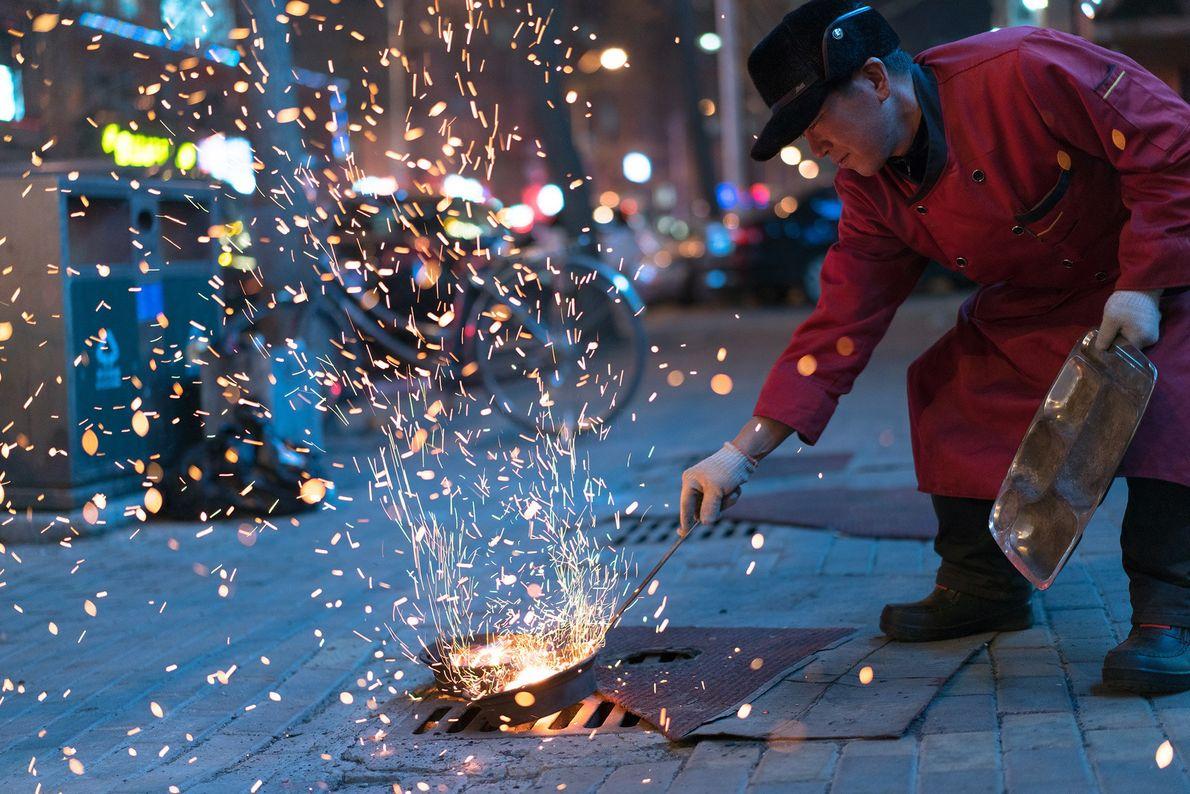 Um homem atiça as brasas de uma churrascaria coreana, em Dandong, na China