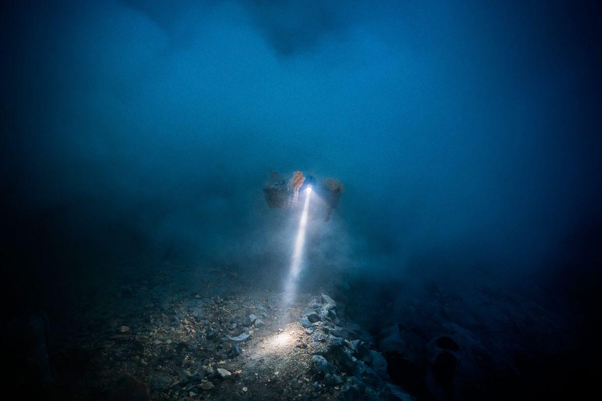 Luz da lanterna do capacete de um mineiro irrompe na escuridão