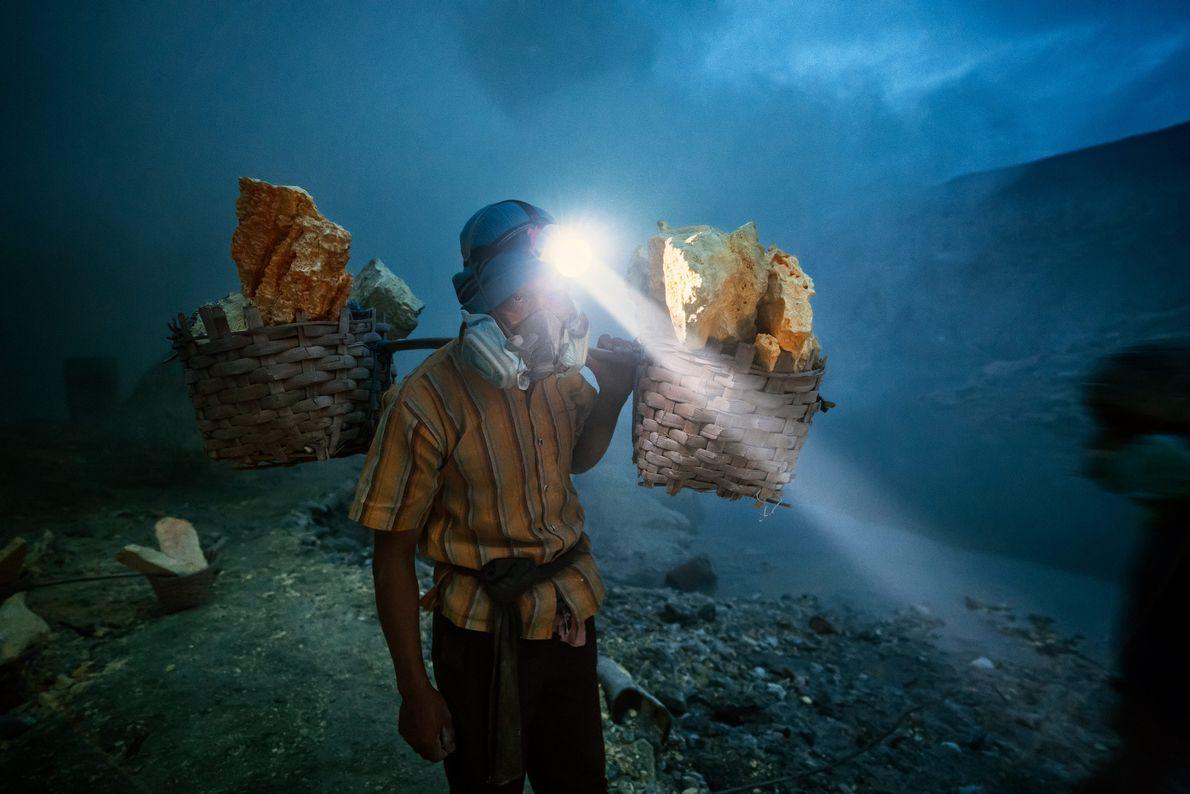 Homem carrega blocos de enxofre extraídos do Monte Ijen