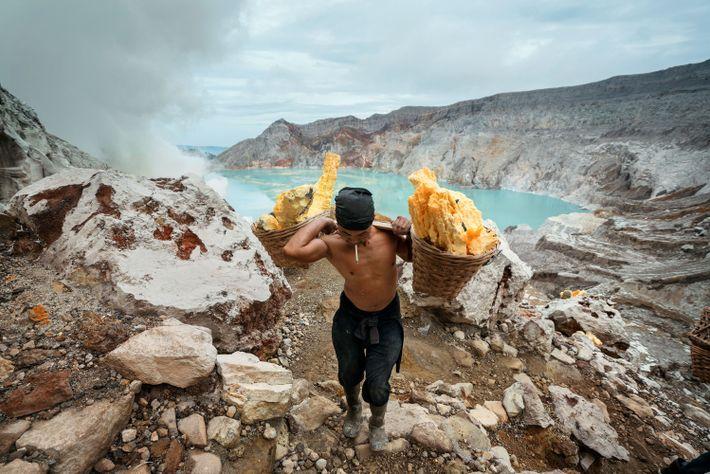 Sunarto, de 41 anos, transporta dois cestos com enxofre