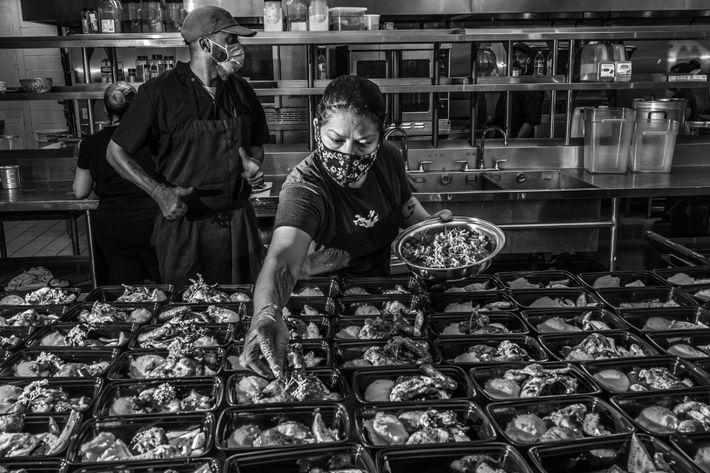 Funcionários do Lucille's 1913, um restaurante móvel sem fins lucrativos gerido por Chris Williams, prepara refeições ...
