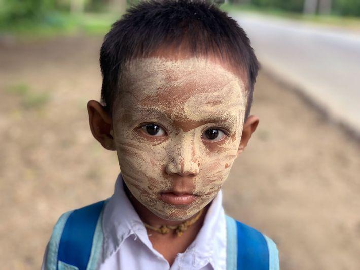 Ar Kar Phyo, 6 anos, tem o rosto coberto por thanaka enquanto se dirige para o ...