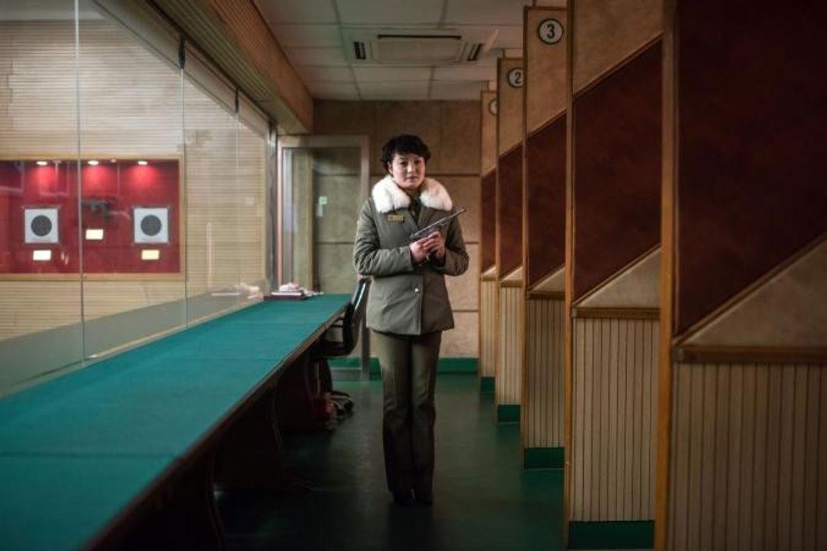 Kim Su Ryon, instrutora de tiro norte-coreana, posa com uma pistola na academia de tiro de ...