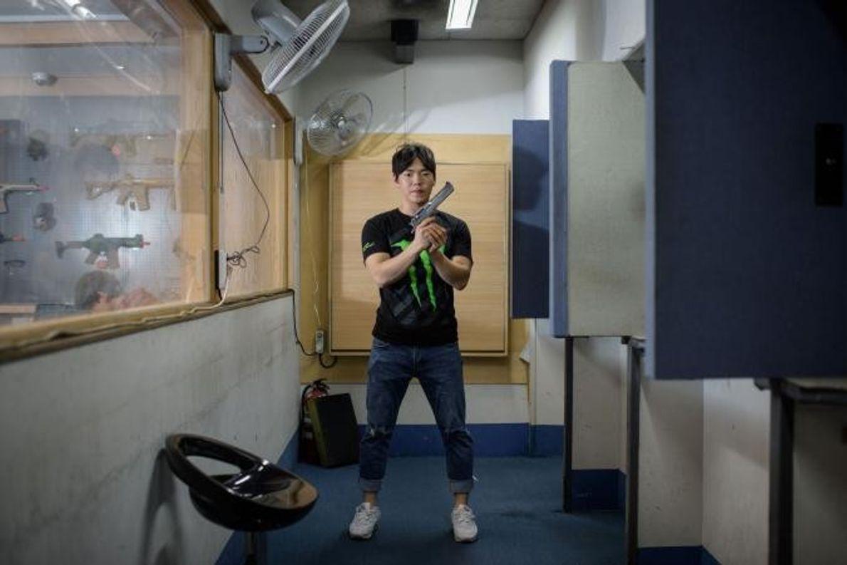 Lee Chi-yoon, instrutor de tiro sul-coreano, posa empunhando uma arma na academia de tiro de Mokdong, ...