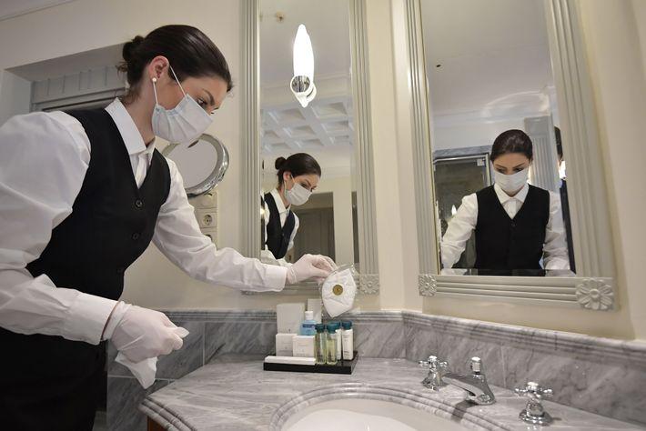 Uma funcionária coloca máscaras faciais na casa de banho de uma das suites do famoso Hotel ...