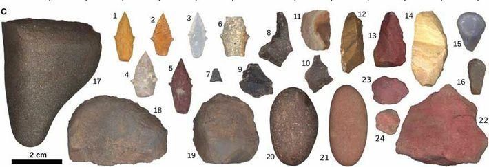 O conjunto de ferramentas encontradas no enterro inclui pontas de projéteis; rochas pesadas que provavelmente eram ...