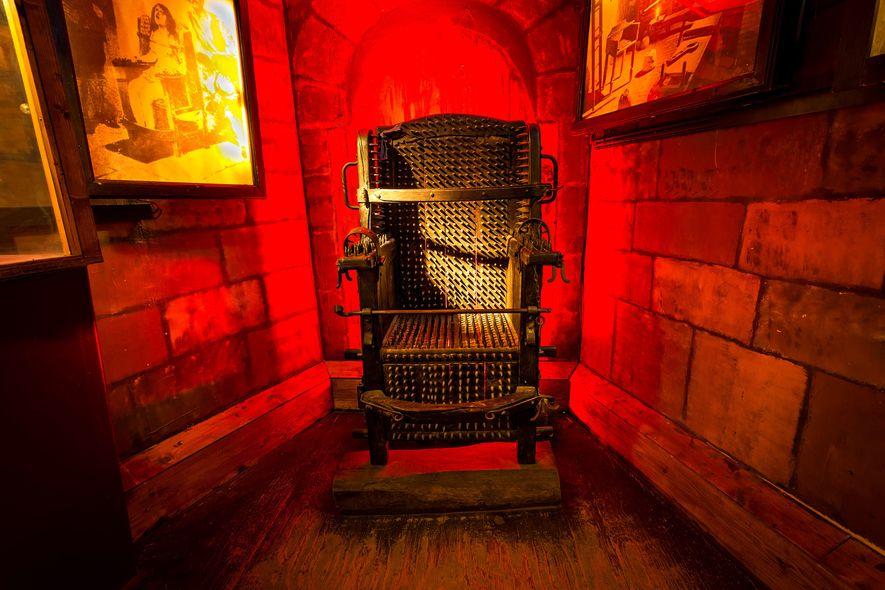 A assustadora cadeira da inquisição do Museu da Tortura com imagens ampliadas de livros e artigos ...