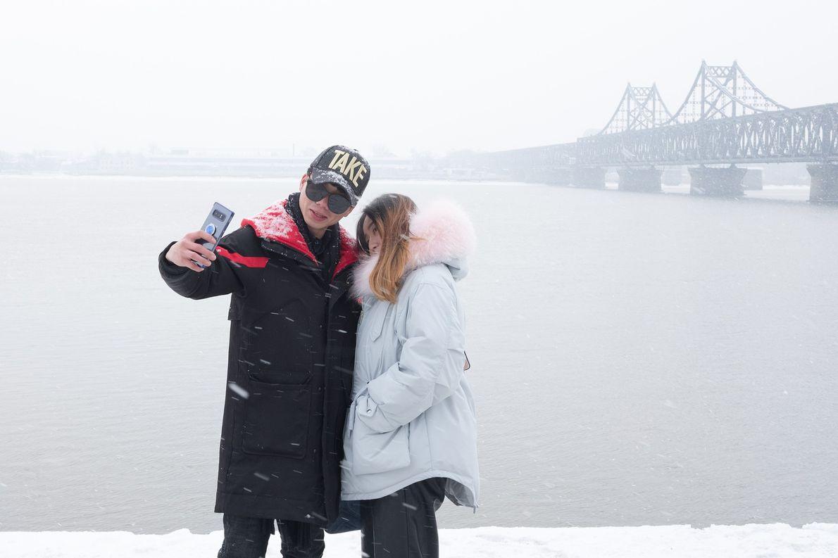 Turistas tiram uma selfie no rio Yalu