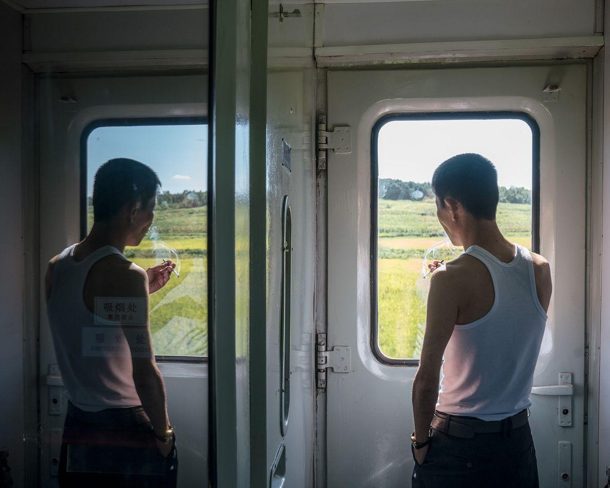 Um passageiro olhando pela janela do comboio entre Pequim e Pyongyang.