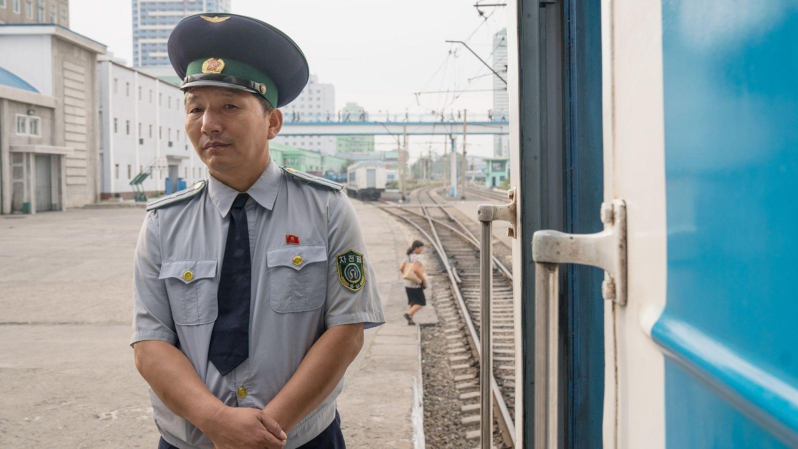 Um trabalhador das linhas férreas na plataforma da estação de comboios de Pyongyang