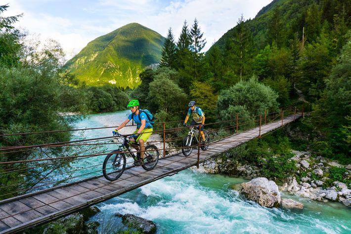 Ciclistas atravessam uma ponte no Rio Soča, na Eslovénia.