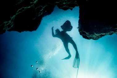 Pescador mergulha à procura de esponjas do mar