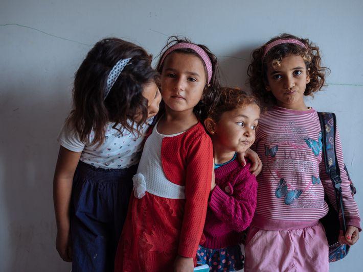 Crianças refugiadas sírias, a posar para a fotografia, na sua sala de aula. A escola, administrada ...