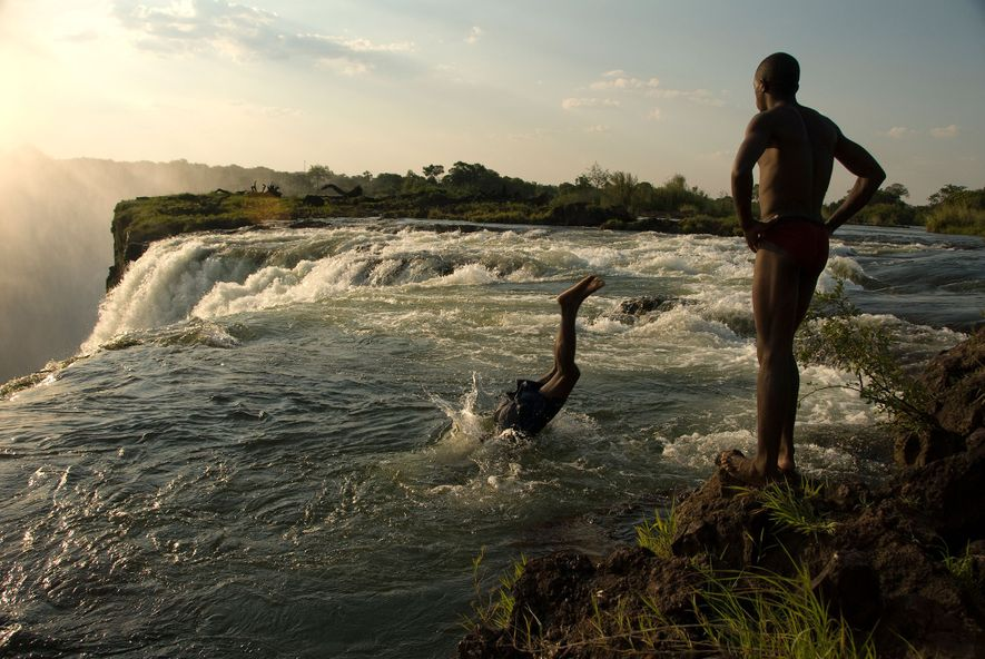 Homens a mergulhar num pequeno lago, no topo das Cataratas de Vitória.