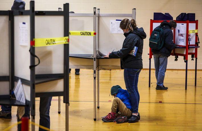 Um menino sentado no chão, junto a uma cabine de voto, enquanto a sua mãe votava ...