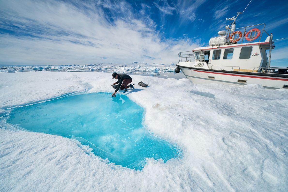 Libecki enche a sua garrafa de água, numa pequena piscina de água derretida, num icebergue. Apesar ...
