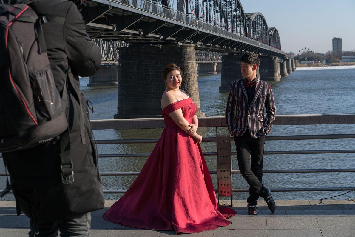 Um casal posa para um retrato de casamento próximo da Ponte da Amizade, em Dandong, na ...