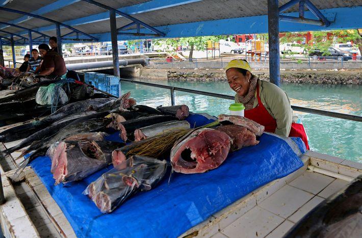 Uma mulher vende peixe num mercado em Suva, nas Ilhas Fiji.