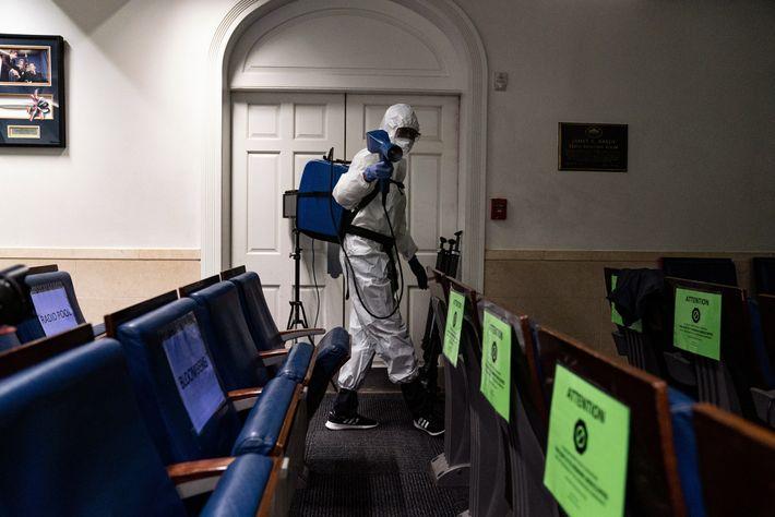 Um membro da equipa de limpeza da Casa Branca pulveriza um desinfetante na sala de Conferências ...