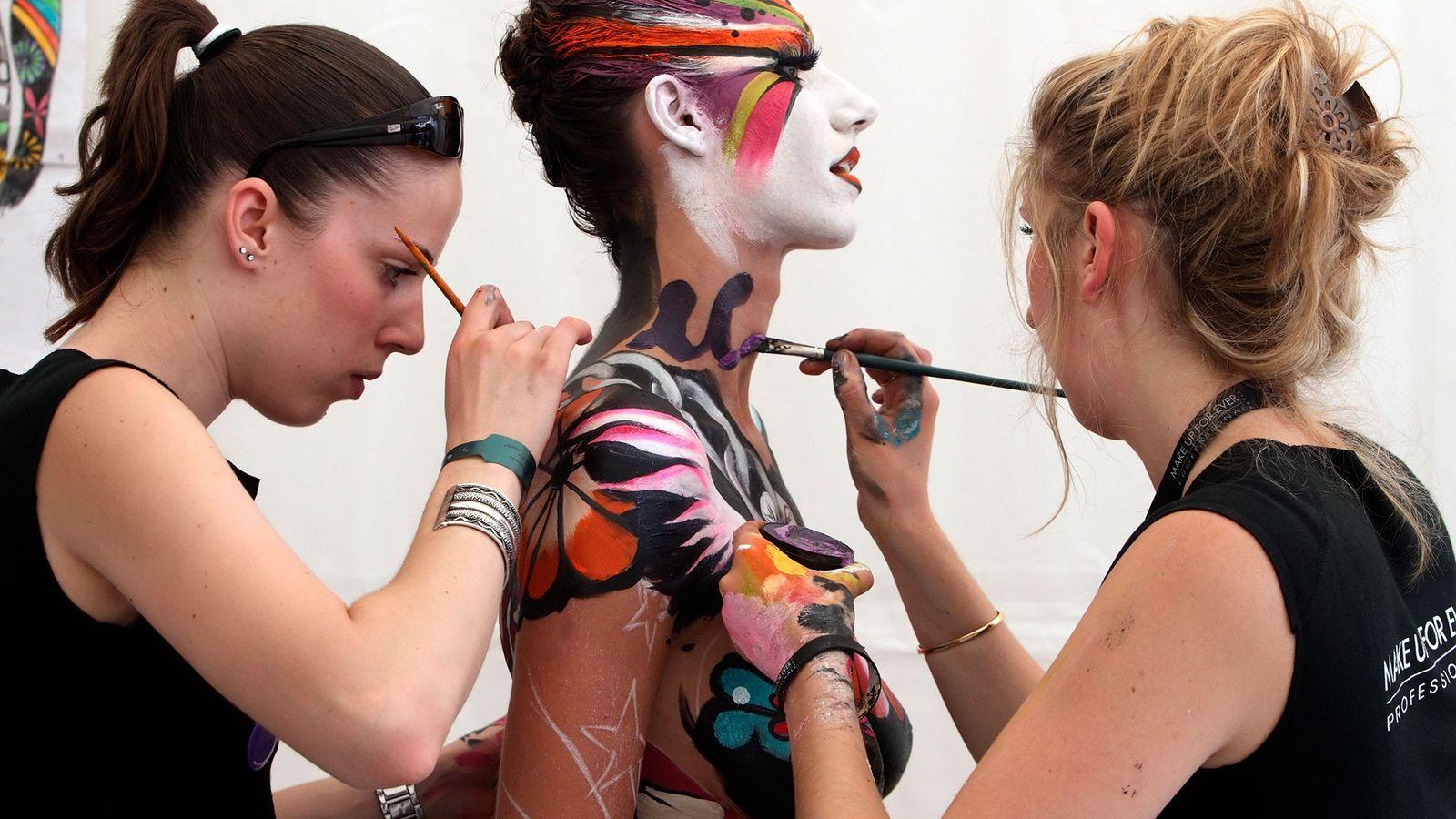 Artistas pintam o corpo de uma modelo